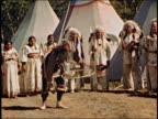 Medium shot Native American man performing hoop dance while group of people watch w/tents in background / AUDIO