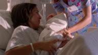 Medium shot nurse handing newborn baby to woman laying in hospital bed