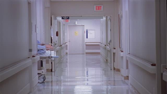 Medium shot nurses pushing patient on gurney down hospital hallway