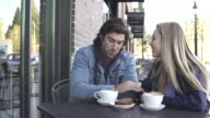 Medium shot of a couple sitting in front of a coffee shop