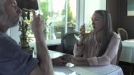 Medium shot of a couple toasting in a restaurant