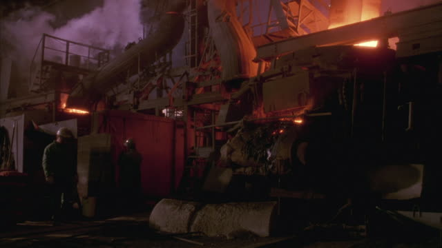 Medium shot of a fiery foundry or factory with sparks and molten steel.