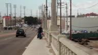 Medium Shot of a homeless man pushing a cart in Los Angeles