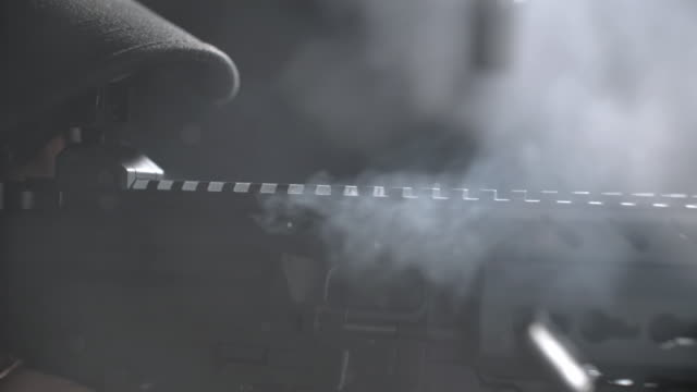 Medium shot of a machine gun being fired on a shooting range; spent shells, cartridges, bullets and smoke are ejected toward camera (ultra slow motion from Phantom Flex).