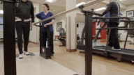 Medium shot of a senior man walking in parallel bars