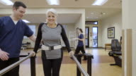 Medium shot of a senior woman walking in parallel bars