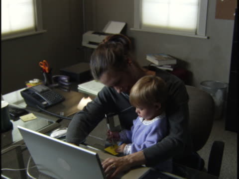 medium shot of a woman in her home office with a child on her lap as she talks on the phone
