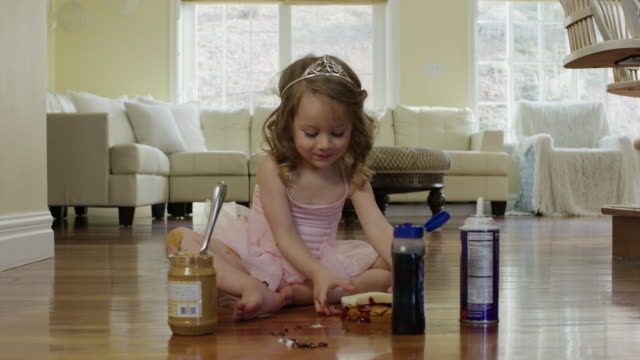 'Medium shot of ballerina girl eating sandwich on floor / Cedar Hills, Utah, United States'