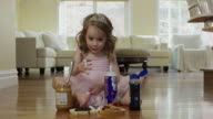 'Medium shot of ballerina girl eating whipped cream on floor / Cedar Hills, Utah, United States'