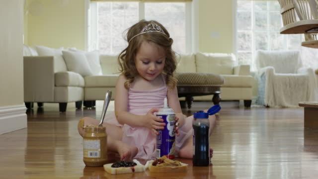 'Medium shot of ballerina girl on floor with whipped cream / Cedar Hills, Utah, United States'