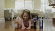 'Medium shot of ballerina girl spreading food on floor / Cedar Hills, Utah, United States'