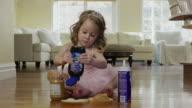 'Medium shot of ballerina girl squeezing jelly onto bread / Cedar Hills, Utah, United States'