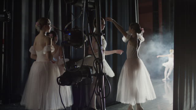 Medium shot of ballerina giving guidance backstage / Salt Lake City, Utah, United States