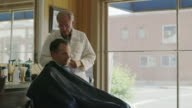 Medium shot of barber clipping hair of customer / Pleasant Grove, Utah, United States