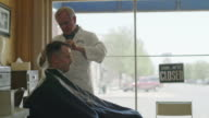 Medium shot of barber cutting hair of customer / Pleasant Grove, Utah, United States