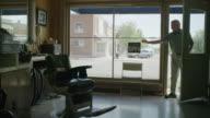 Medium shot of barber entering and opening shop / Pleasant Grove, Utah, United States