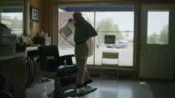 Medium shot of barber putting on jacket / Pleasant Grove, Utah, United States