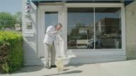 Medium shot of barber sweeping sidewalk in front of shop / Pleasant Grove, Utah, United States
