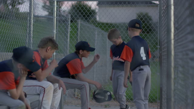 Medium shot of baseball team comforting unhappy batter / American Fork, Utah, United States