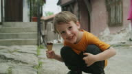 Medium shot of boy with messy face eating ice cream cone in street / Plovdiv, Bulgaria