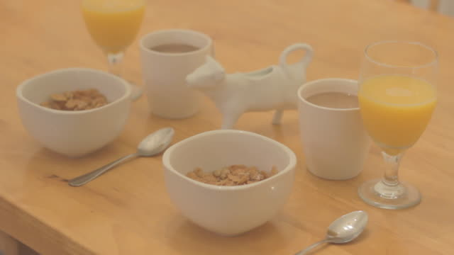 Medium shot of cereal, coffee, and orange juice arranged for breakfast.