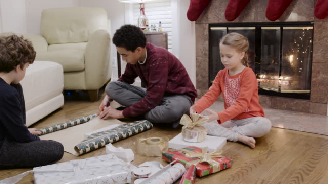 Medium shot of children wrapping a gift for Christmas