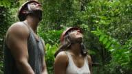 Medium shot of couple admiring zipliners in rain forest / Quepos, Puntarenas, Costa Rica