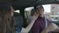 Medium shot of couple enjoying music in car / Provo, Utah, United States