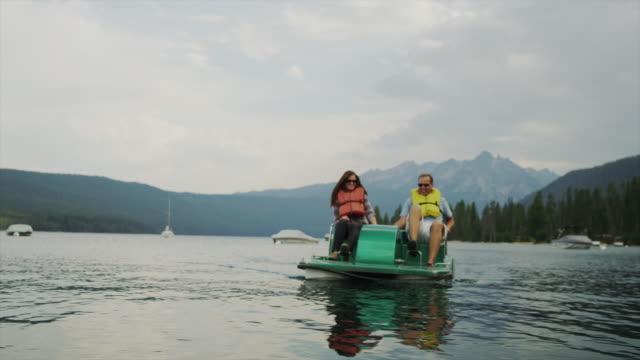 Medium shot of couple in pedal boat on lake / Redfish Lake, Idaho, United States