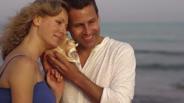 Medium shot of couple listening to conch shell/Marbella region, Spain