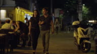 Medium shot of couple walking at night and entering restaurant / Berlin, Germany