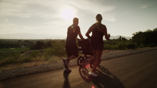 Medium shot of couple with baby carriage running on sunny road / Cedar Hills, Utah, United States