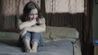 Medium shot of domestic abuse victim crying on bed / Springville, Utah, United States