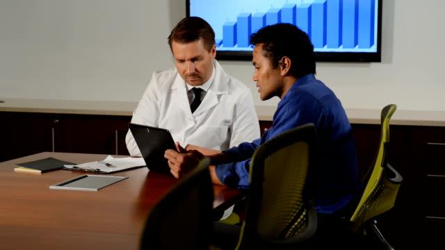 Medium Shot of Ethnic Businessman Using Digital Tablet in Meeting