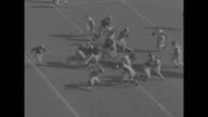 Medium shot of field as Tom Harmon of Michigan Wolverines punts to Penn Quakers in opening period of game / Harold Lockhart of Michigan fumbles...