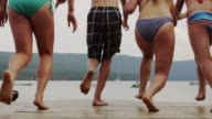 Medium shot of friends on dock running and jumping into lake / Redfish Lake, Idaho, United States