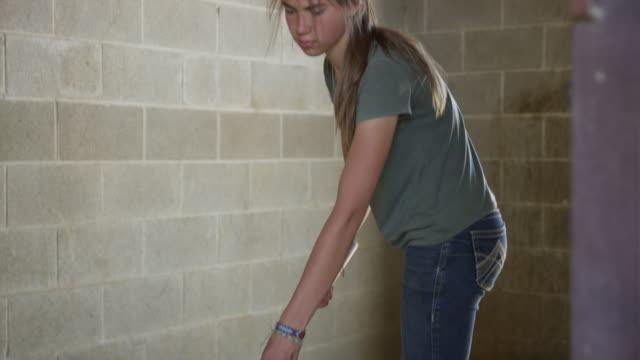 Medium shot of girl cleaning floor of stable / Lehi, Utah, United States