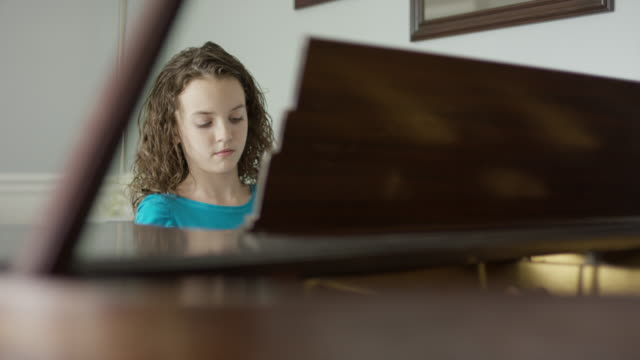 Medium shot of girl practicing piano / Provo, Utah, United States