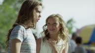 Medium shot of girls whispering at funfair / Pleasant Grove, Utah, United States