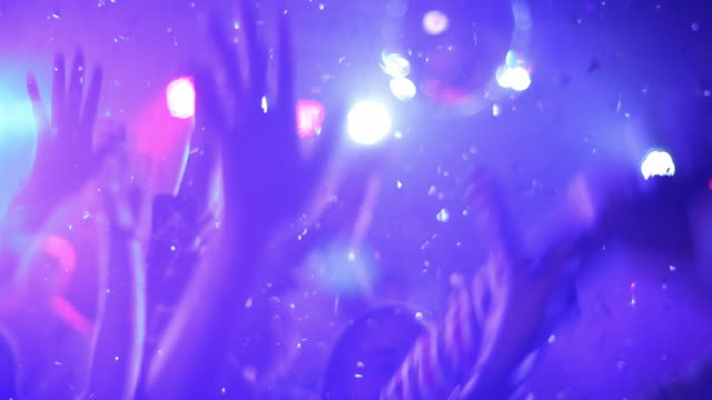Medium shot of hands dancing under glitter confetti