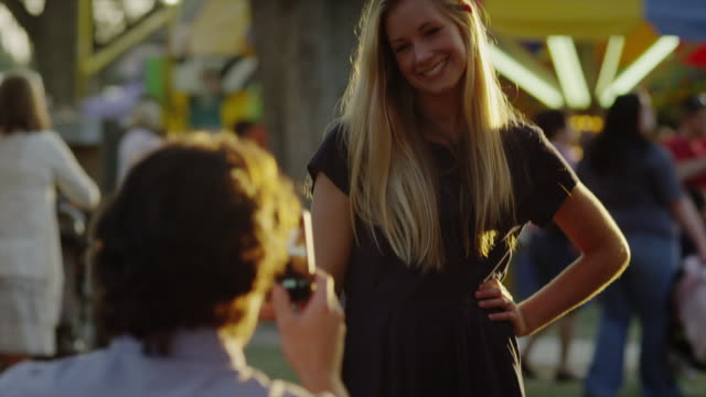 Medium shot of man photographing girlfriend at carnival / American Fork, Utah, United States