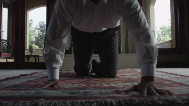 Medium shot of man unrolling rug in living room / Cedar Hills, Utah, United States