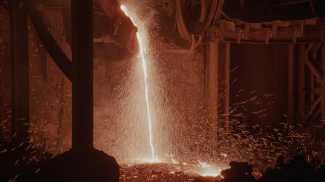 Medium shot of molten steel pouring out of a crucible.