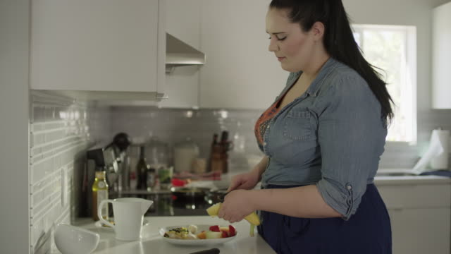 Medium shot of overweight woman preparing healthy meal / Orem, Utah, United States