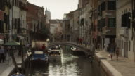 Medium shot of people crossing bridge on Venetian canal / Venice, Italy