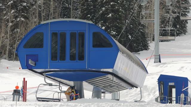 medium shot of people get on a ski lift at a mountain near salt lake city, utah