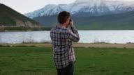 Medium shot of Photographer at mountain lake
