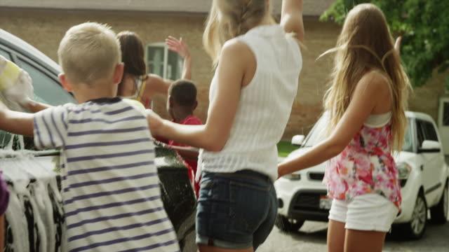 Medium shot of playful children washing car / Pleasant Grove, Utah, United States