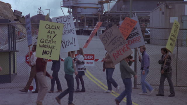 Medium shot of protestors waving signs about cleaner air outside of an industrial power plant.