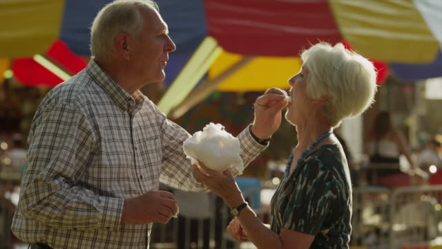 Medium shot of senior couple eating cotton candy at carnival / American Fork, Utah, United States